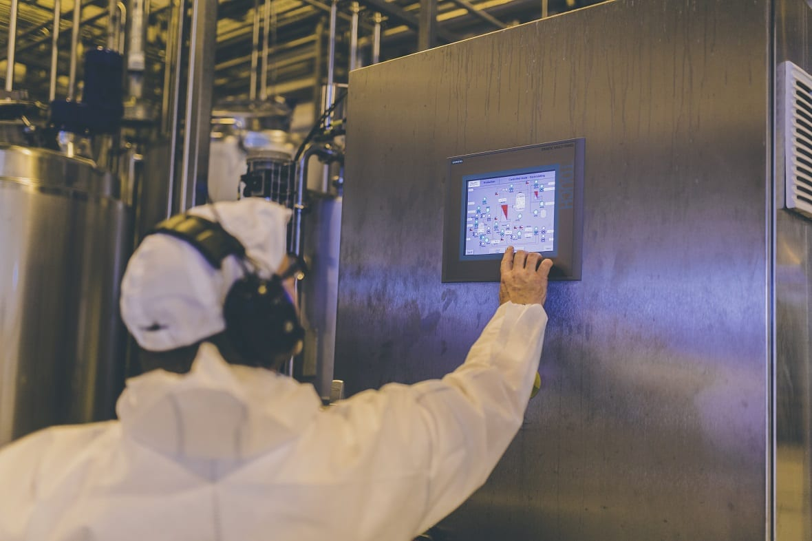 Person pointing on a small screen in a factory